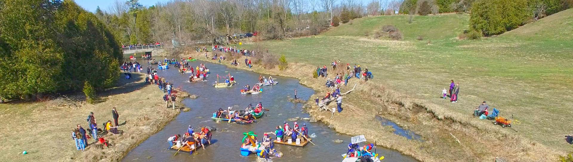 Drone shot of crazy water craft going down Ganaraska River in Spring with blue skies
