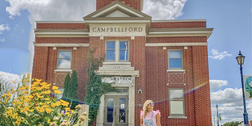 Woman standing in front of town hall in Campbellford on a summer day with blue skies