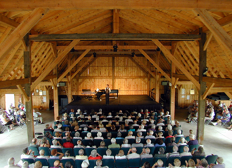 Interior of theatrical barn with stage and audience