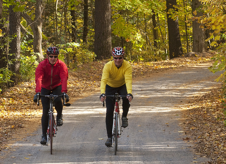 Two men cycling through fall forest