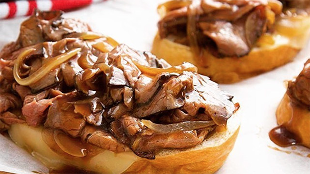 hot beef sandwich with onions on table