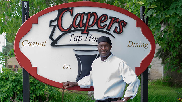 Chef standing in front of sign for Capers Tap House