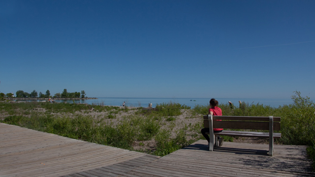 Woman sitting on bench at edge of boardwalk near lake