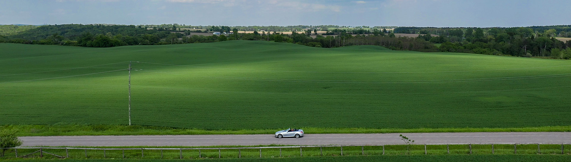 Drone view of car driving down road in front of green fields