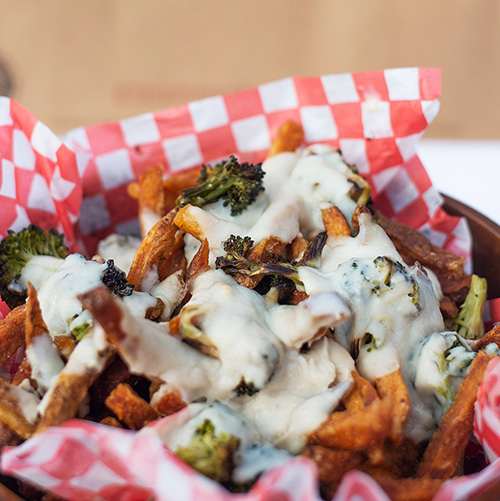 Poutine in basket lined with red-checked paper