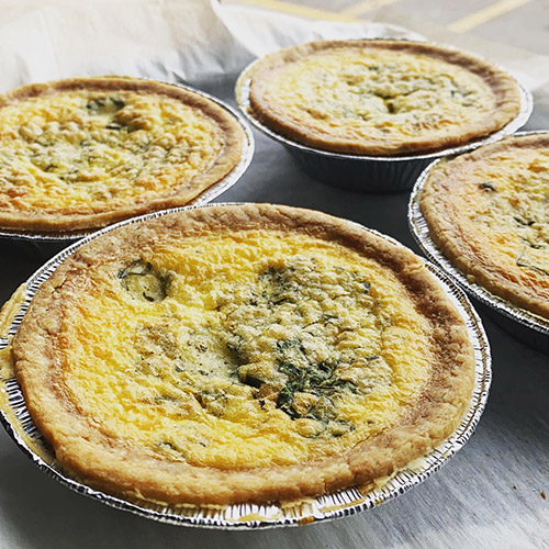 4 fresh quiche in pie plates at local bakery