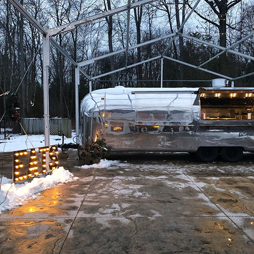 Silver airstream food truck set up for takeout in winter