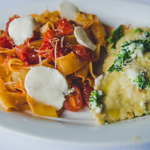 Pasta dishes with cheese, tomatoes and spinach on white plate