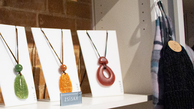 Necklaces with colourful pendants on display boards in retail shop