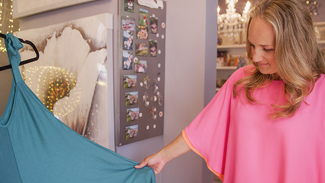 Woman in bright pink shirt looking at teal summer dress in retail store