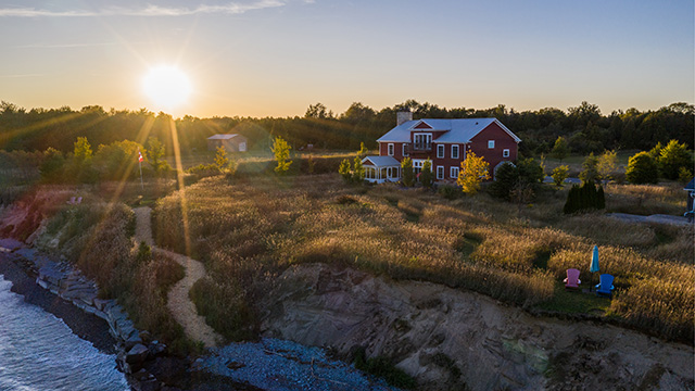 Drone view of retreat centre at sunset with path leading to lakefront bluffs and beach with wooded setting in background