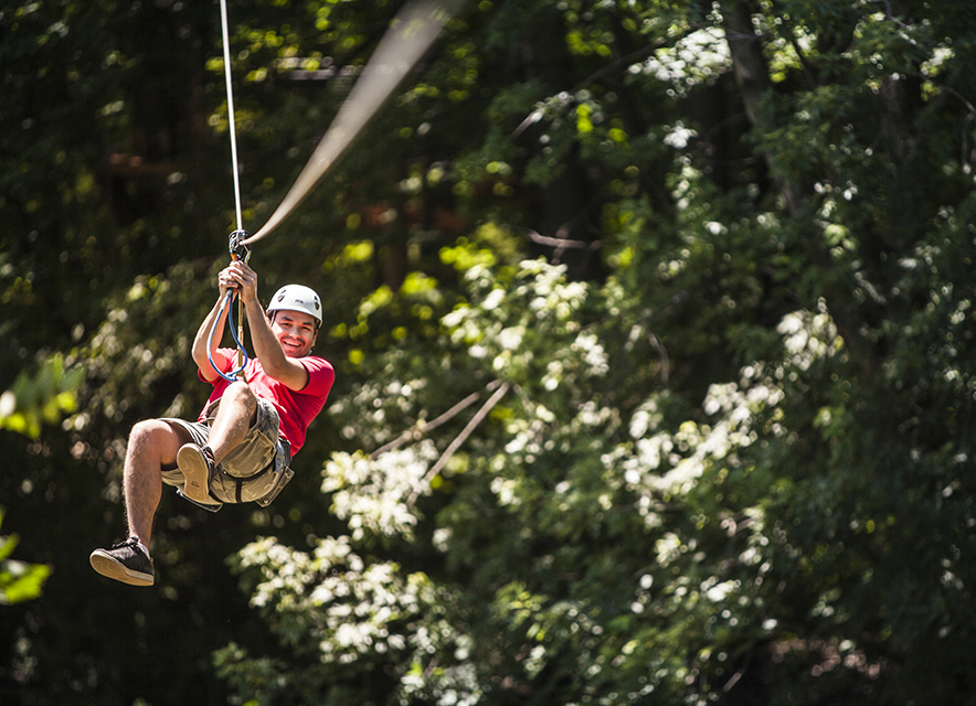 Man on zipline at Treetop Trekking
