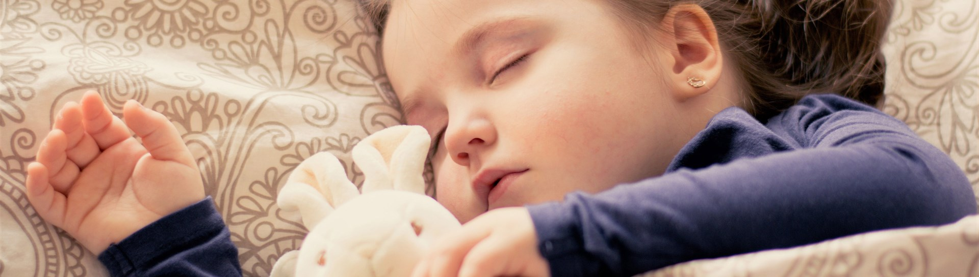 Young child snuggling with stuffed bunny while sleeping