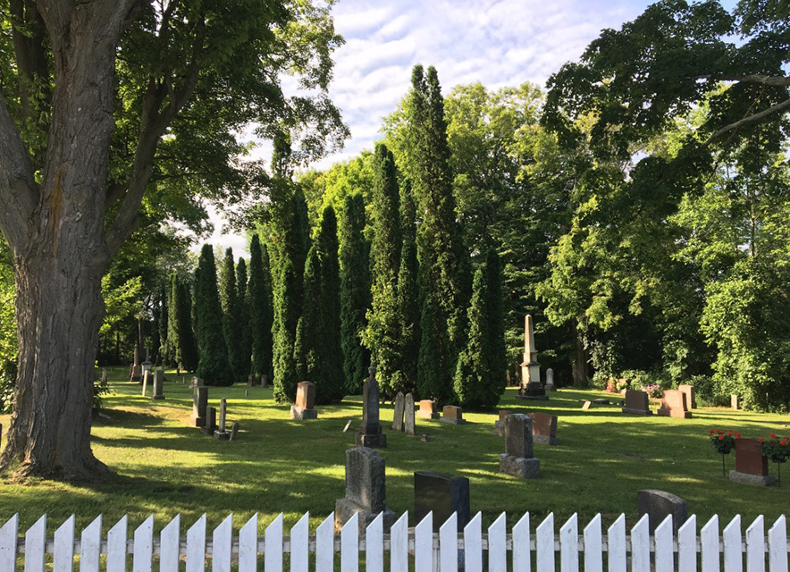 Cemetery with long shadows in summer and white picket fence in foreground