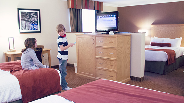 Boy and girl in large hotel room watching television