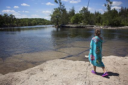 Girl looking out on swimming hole while wrapped in brightly coloured towel