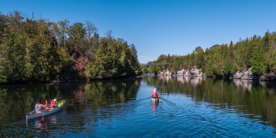 2 canoes carrying 2 people paddling down the Trent River towards the Ranney Gorge Suspension Bridge in summer