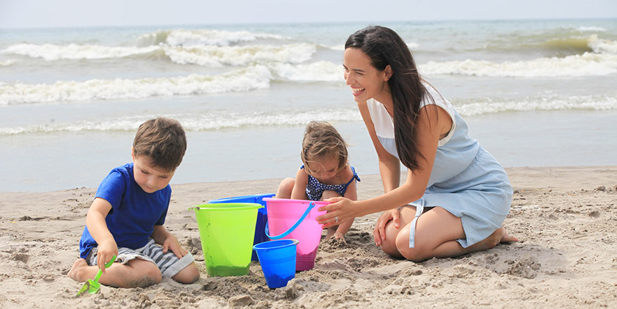 Mother and two children making sandcastles at the beach