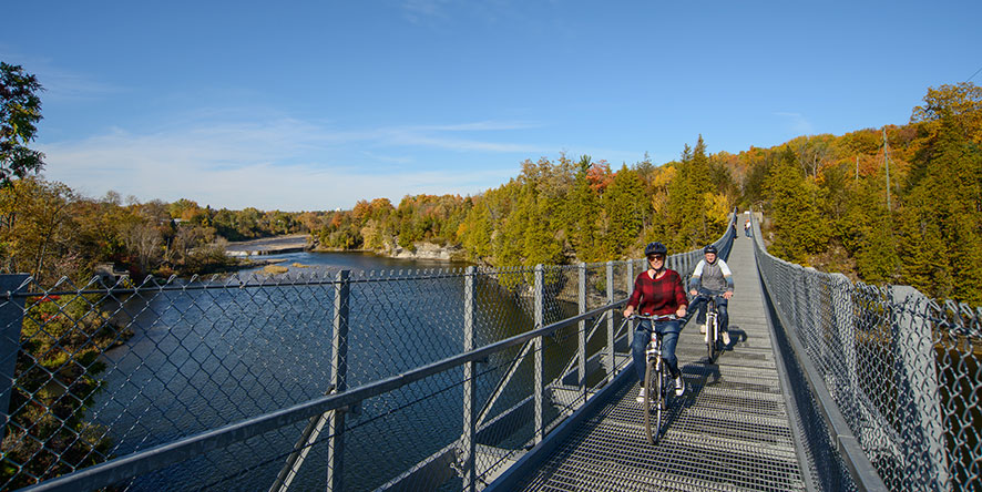 Couple riding bikes over the Ranney Gorge Suspension Bridge in fall
