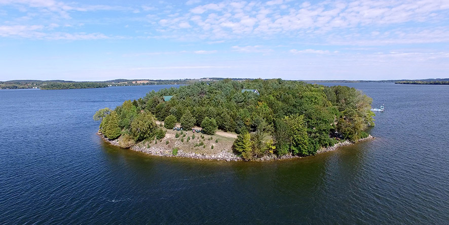 Drone view of small island in the middle of a lake in the summertime showing small buildings on island