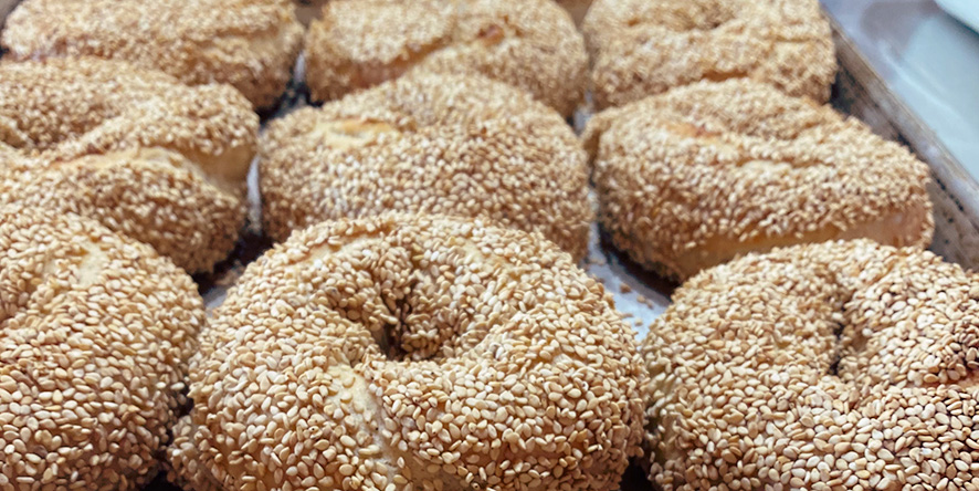 Tray of freshly baked, locally made sesame seed bagels