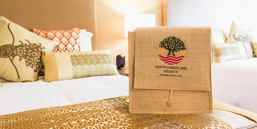 tote bag with Northumberland Heights logo on it sitting on a bed with white linens in a hotel suite