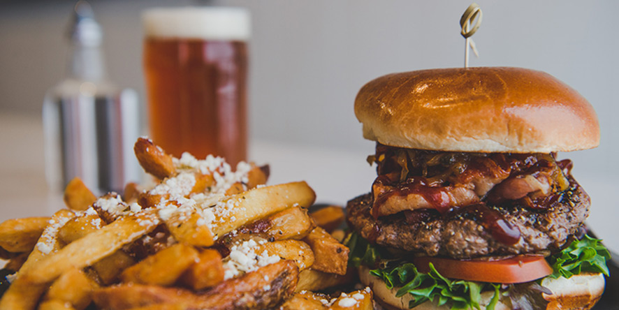 hamburger and french fries on platter at restaurant with beer in background