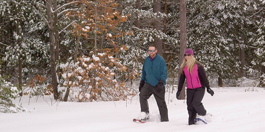 Couple snowshoeing on wooded trail in winter