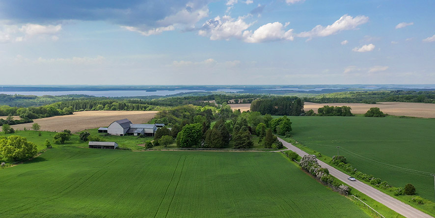 Drone view of farm land in Spring with lush green farm fields