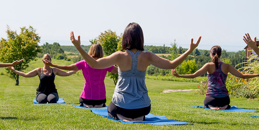 Group of women doing yoga on the grass outside in the summer with view of rolling hills