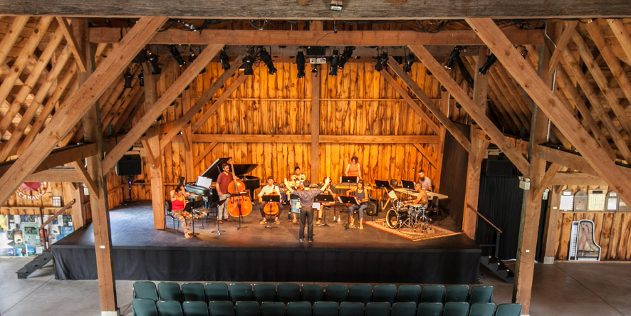 Interior of Westben barn with performers rehearsing on stage
