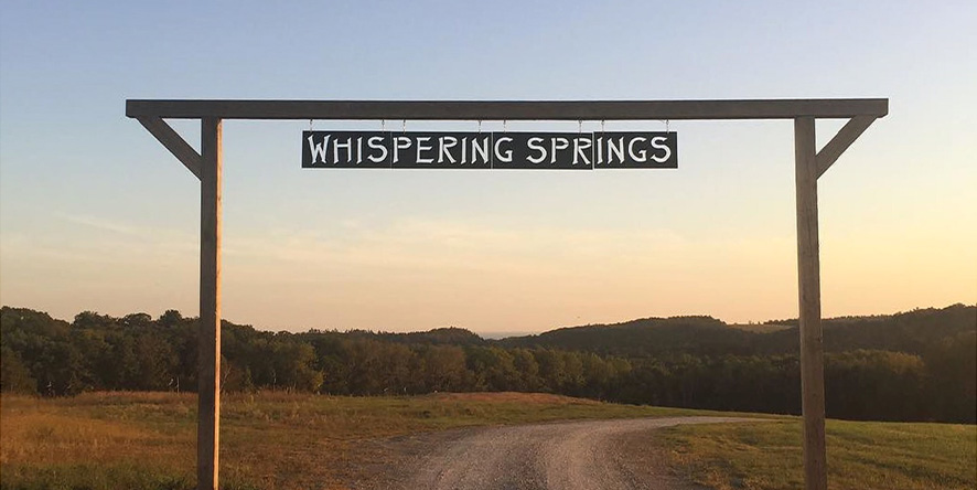 Entrance sign to Whispering Springs glamping resort with colourful sunset
