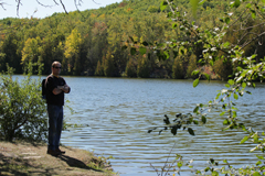 Man standing beside Trent River at Ferris boat launch