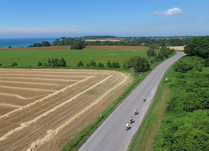 Drone image of cyclists riding on country road with fields and Lake Ontario in background