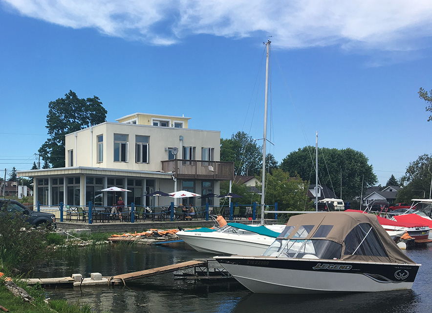 Harbourview Cafe exterior with summer patio and boats in harbour