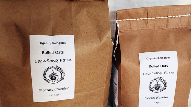 Brown bags of organic oats from Loon Song Farms