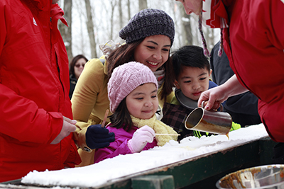 Family making snow taffy at outdoor maple syrup festival