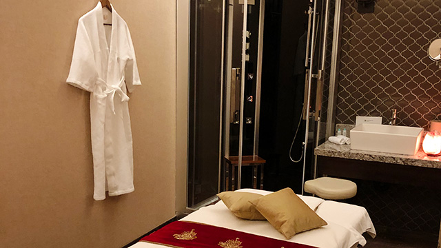 Treatment room at spa with massage table, white robe hanging on the wall and steam shower