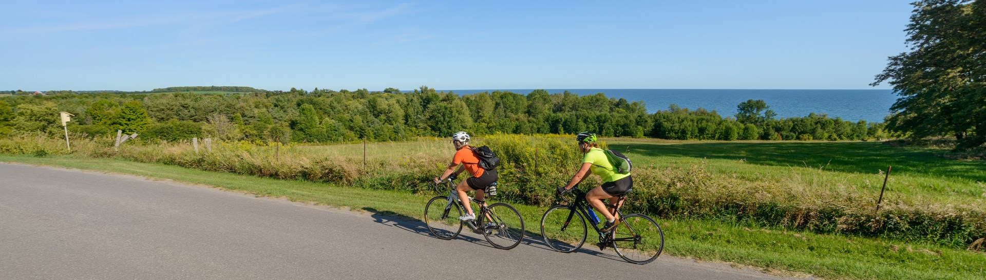 2 female cyclists riding along Lakeshore Drive on a summer day with lake and blue sky in background