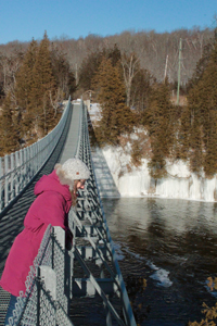 woman on bridge in winter looking down at the river