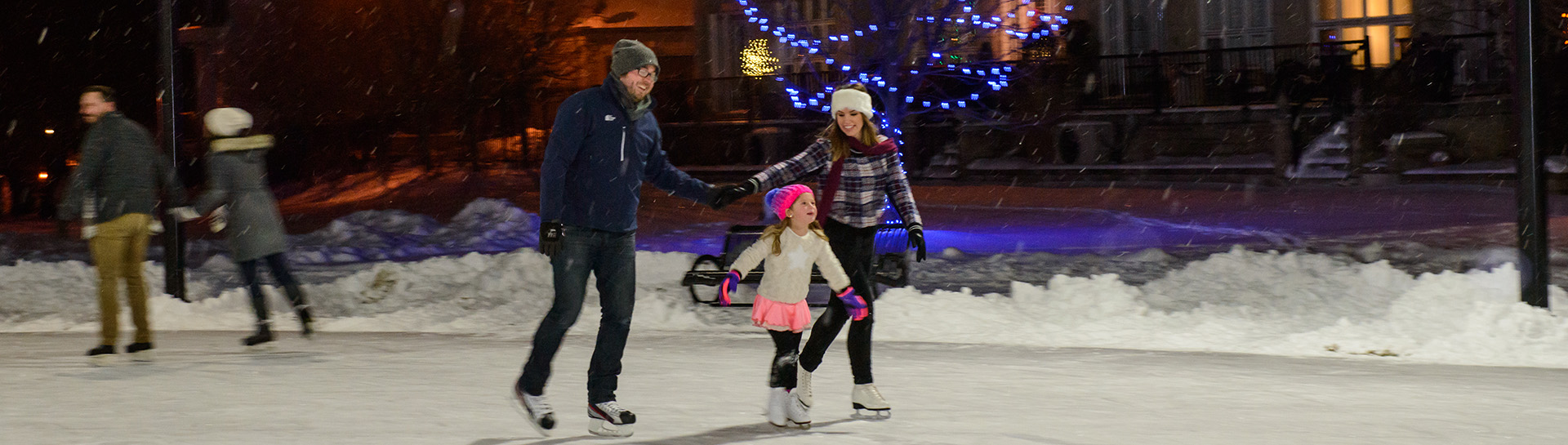 mother and father with young daughter skating on outdoor rink with Christmas lights at night