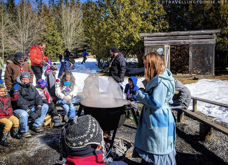 Group of kids around maple syrup kettle with educator