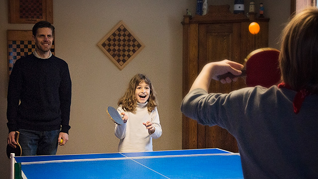 Young girl and father smiling while playing ping pong in games room