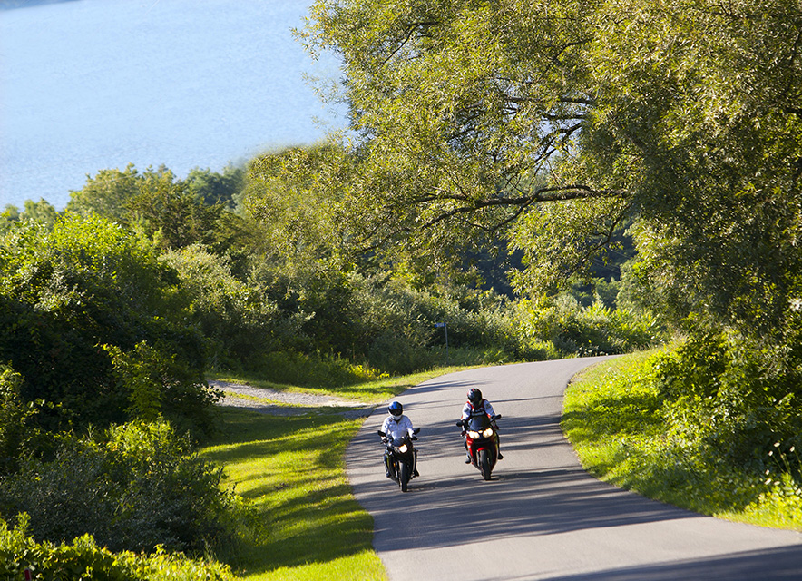 Two people riding motorcycles on tree-lined, hilly road with lake in background