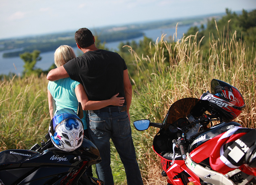 Couple standing near motorcycles looking at view of rolling hills and lake