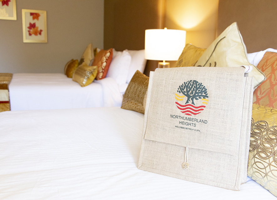 Promotional bag for Northumberland Heights Wellness Retreat sitting on bed in guest room