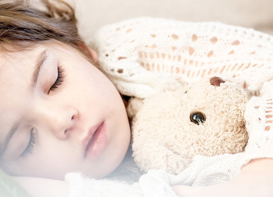 Child sleeping on bed with teddy bear