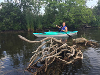 driftwood and woman in kayak
