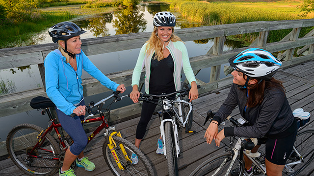 3 women resting on bikes on bridge
