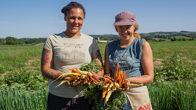 Two female farmers holding carrots